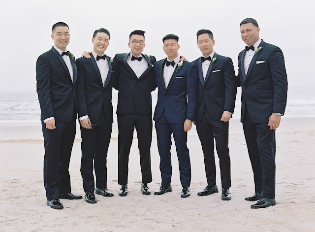 The groom Christopher with the groomsmen on the beach before the wedding