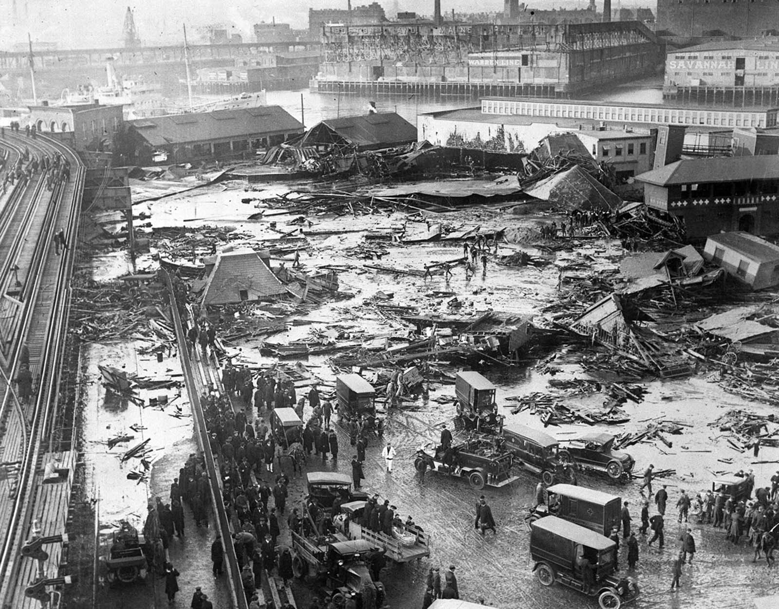 This aerial view shows the site of the molasses storage tank explosion in the section of Commercial St. between Copps Hill and the playground of North End Park in Boston, Massachusetts, on January 15, 1919. The explosion of the steel vat, ninety feet in diameter and fifty-two feet in height, caused 2.3 million gallons of molasses to flood the area, killing 21 people and injuring 150. In the background is the Navy Yard in Charlestown.