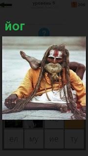 На земле сидит йог в странной позе со спутанными волосами и с бородой