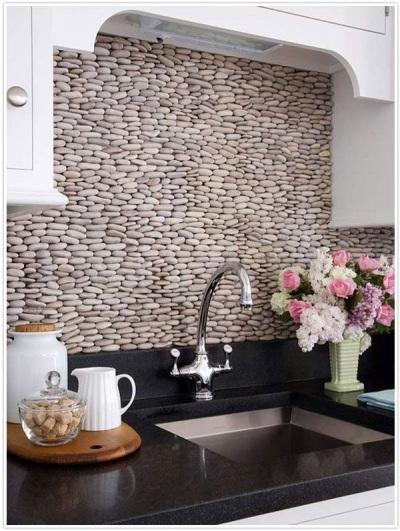 Gunakan batu-batu berwarna cerah untuk menghias dinding di belakang wastafel dapur.
