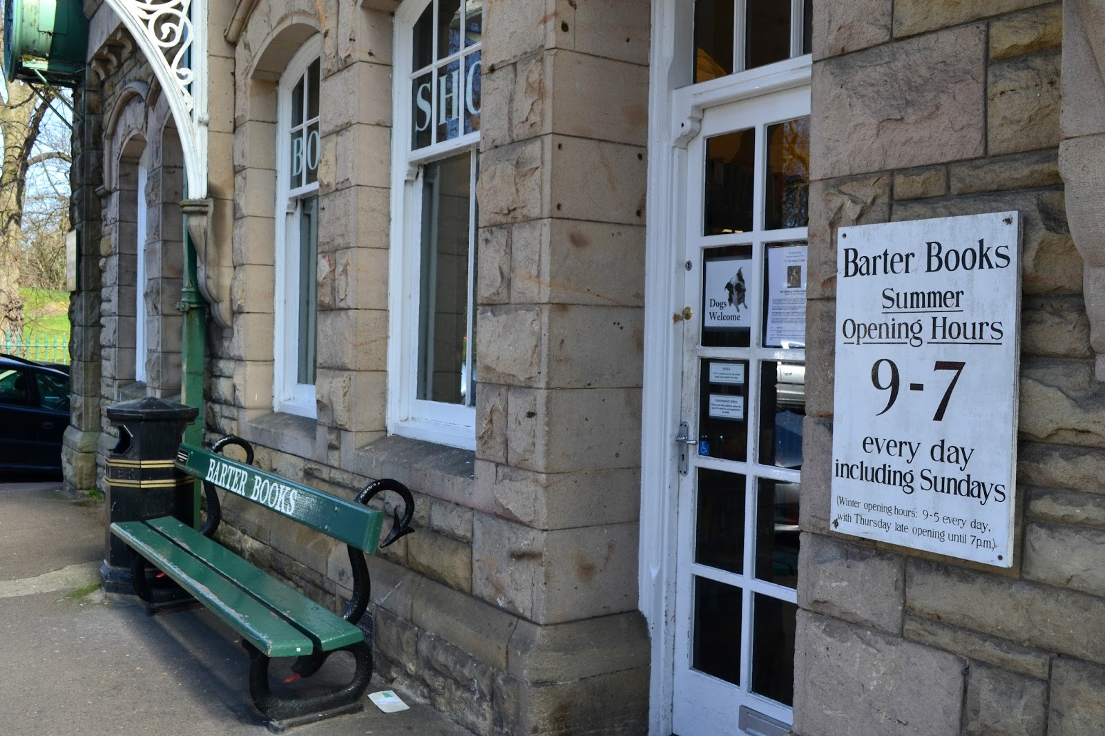 The outside of Barter Books with the opening times and bench
