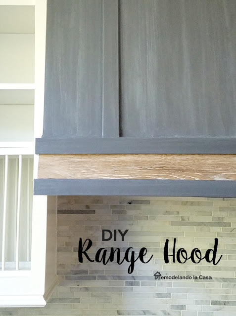 grey whitewashed range hood with wooden band