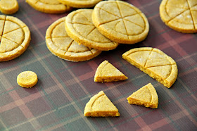 Round dog treats stamped to look like pies, with one treat broken apart into slices