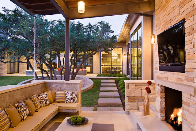 Photo of covered outdoor terrace with the fireplace, tv and siting are with small pillows