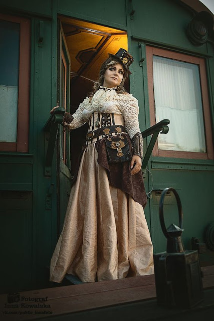 Woman wearing steampunk clothing in cream and taupe. Lace blouse, long skirt, top hat.