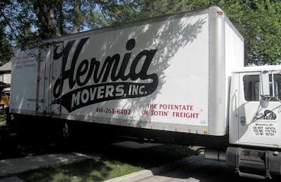 White truck with large script lettering Hernia Movers