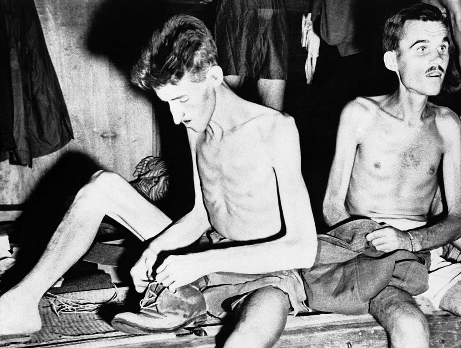 Gaunt and emaciated, but happy at their release from Japanese captivity, two Allied prisoners pack their meager belongings, after being freed near Yokohama, Japan, on September 11, 1945, by men of an American mercy squadron of the U.S. Navy.