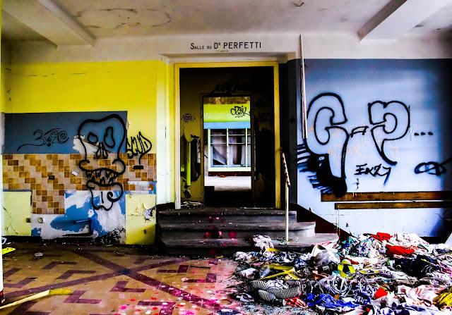 photo de l'ancienne salle d attente du docteur du sanatorium plein de tags plein de vetements par terre cassé delabré