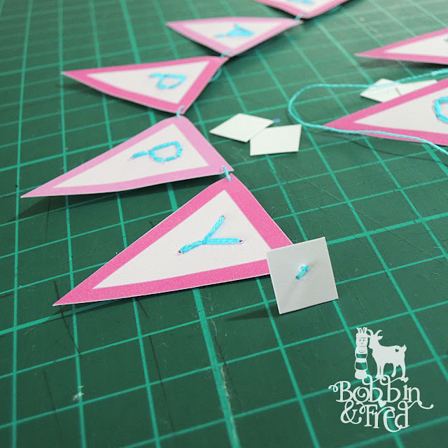 Embroidered card bunting being strung to stick inside a greetings card
