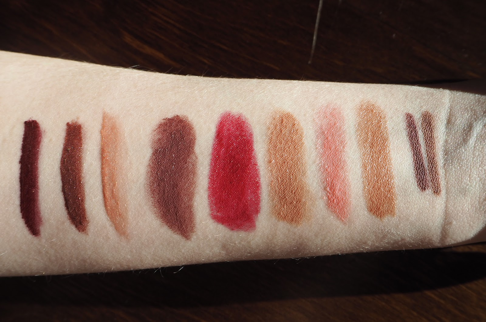 Revlon Swatches Left to right: Ultra HD Matte Lipcolour in Infatuation, Ultra HD Metallic Matte Lipcolours in Shine and Gleam, Super Lustrous Lipsticks in Naughty Plum, Bombshell Red and Bare Affair, Ultra HD Gel Lipcolour in Pink Cloud and Sand and Colourstay Lipliners in Plum and Nude.