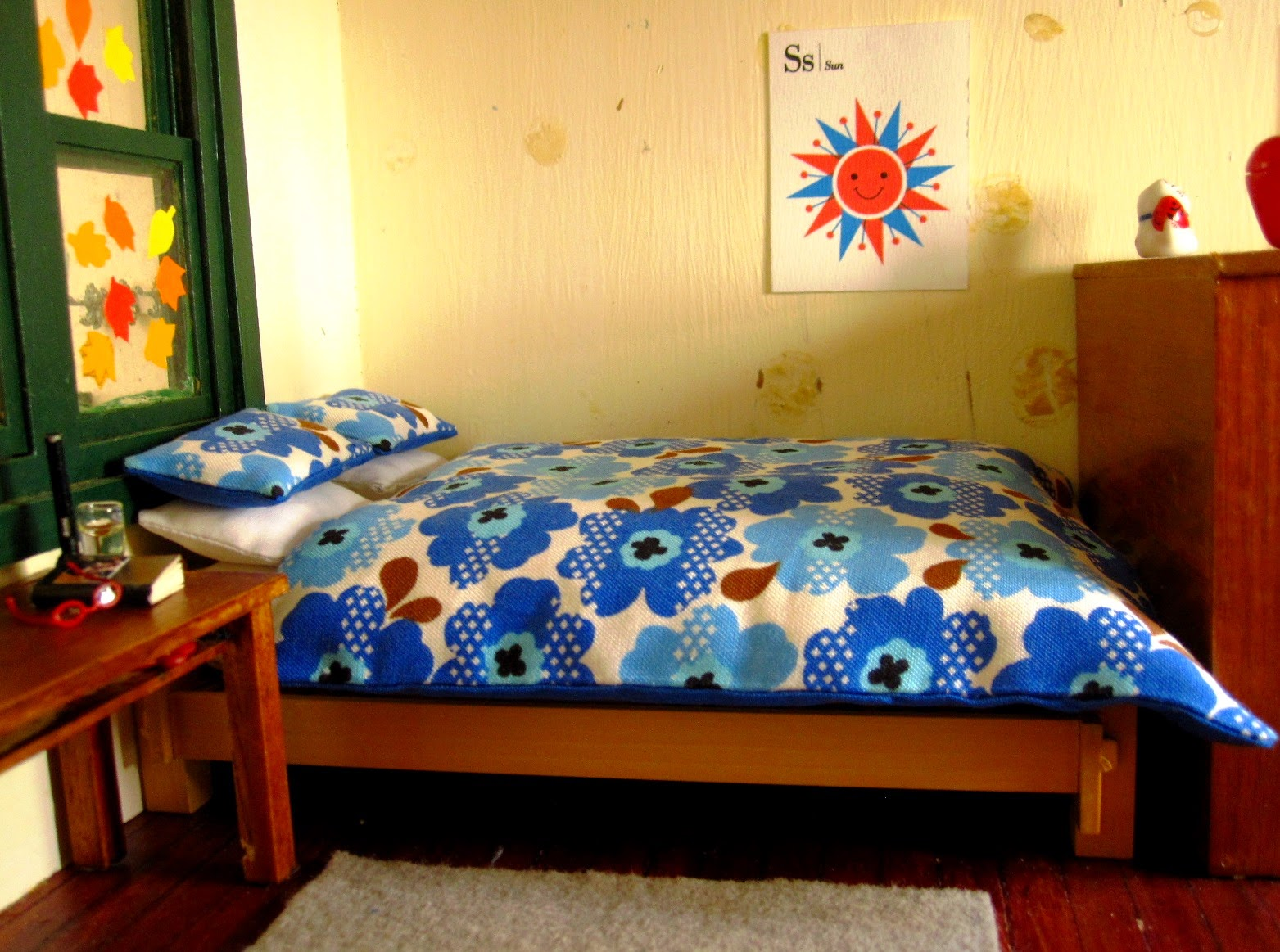 Bed with Marimekko-esque bedding in the corner of a miniature holiday house.