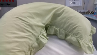 A boomerang pillow with a pale green ruffled pillowcase, placed upon the plain white hospital bed.