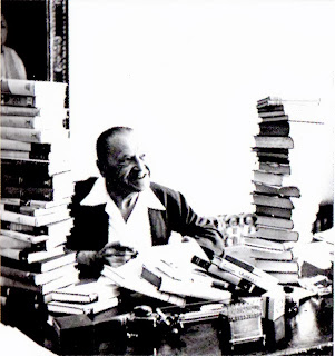 photo of Maugham at his desk, with his productions piled up