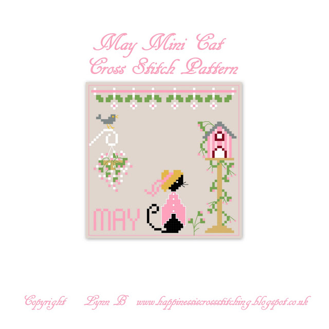 Mini Black cat cross stitch pattern for the May calendar, includes a hanging basket of flowers, Miss Mini Cat with a straw hat stood next to a bird table trimmed with flowers