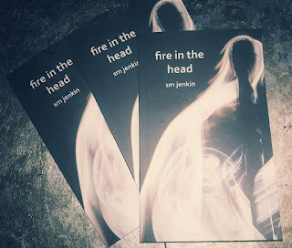 multiple copies of fire int he head book on a table