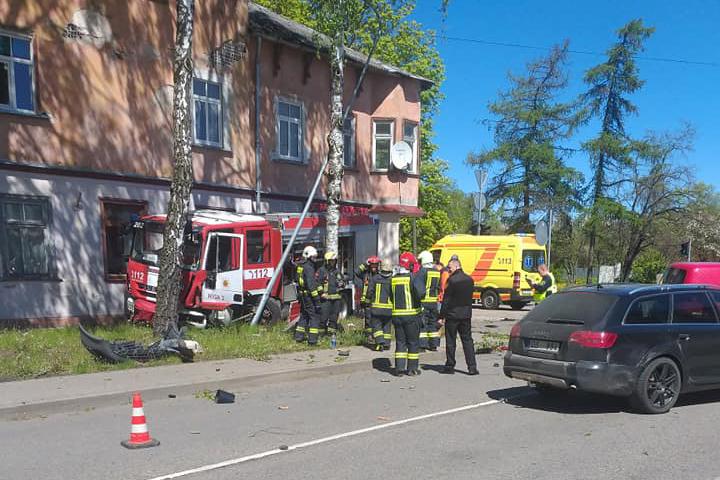 Ugunsdzēsēji glābēji stāv ap avarējušo auto