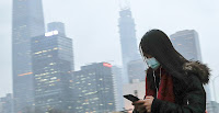 Woman wearing a mask walks to a subway in Beijing. Photo credit: Andy Wong/Associated Press