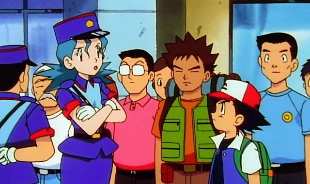 Uniforme todos azul y violeta, se ve al fondo un agente de policía hombre