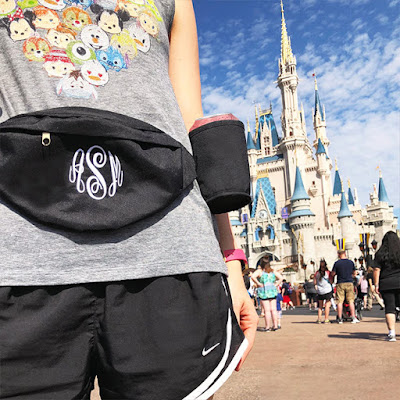 monogrammed black fanny pack in front of cinderella's castle at disney