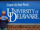 Joe holding the book in front of a wall with a large sign / logo that says Dare to be first. University of Delaware