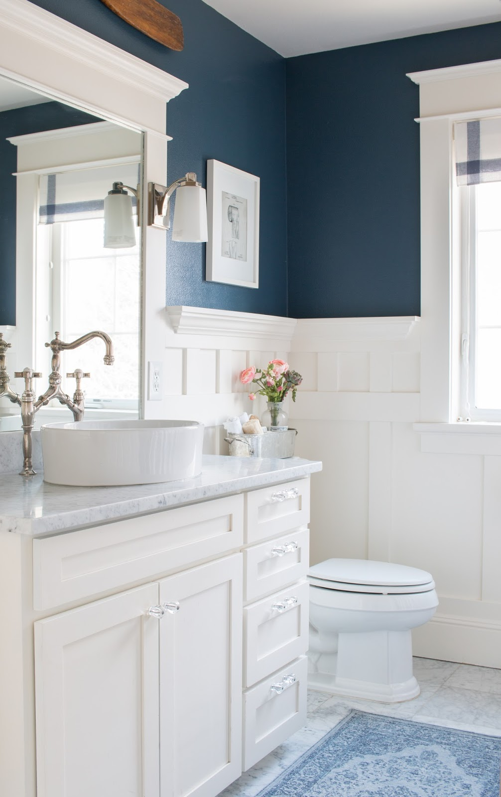 navy blue walls with a white vanity with marble counter and floors