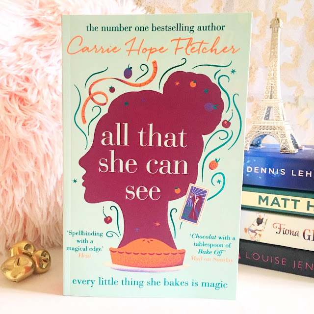 All that she can see by Carrie Hope Fletcher in the centre. Stack of books in the background on the right side with a silver eiffel tower ornament placed on top. Pink fluffy pillow in the left background