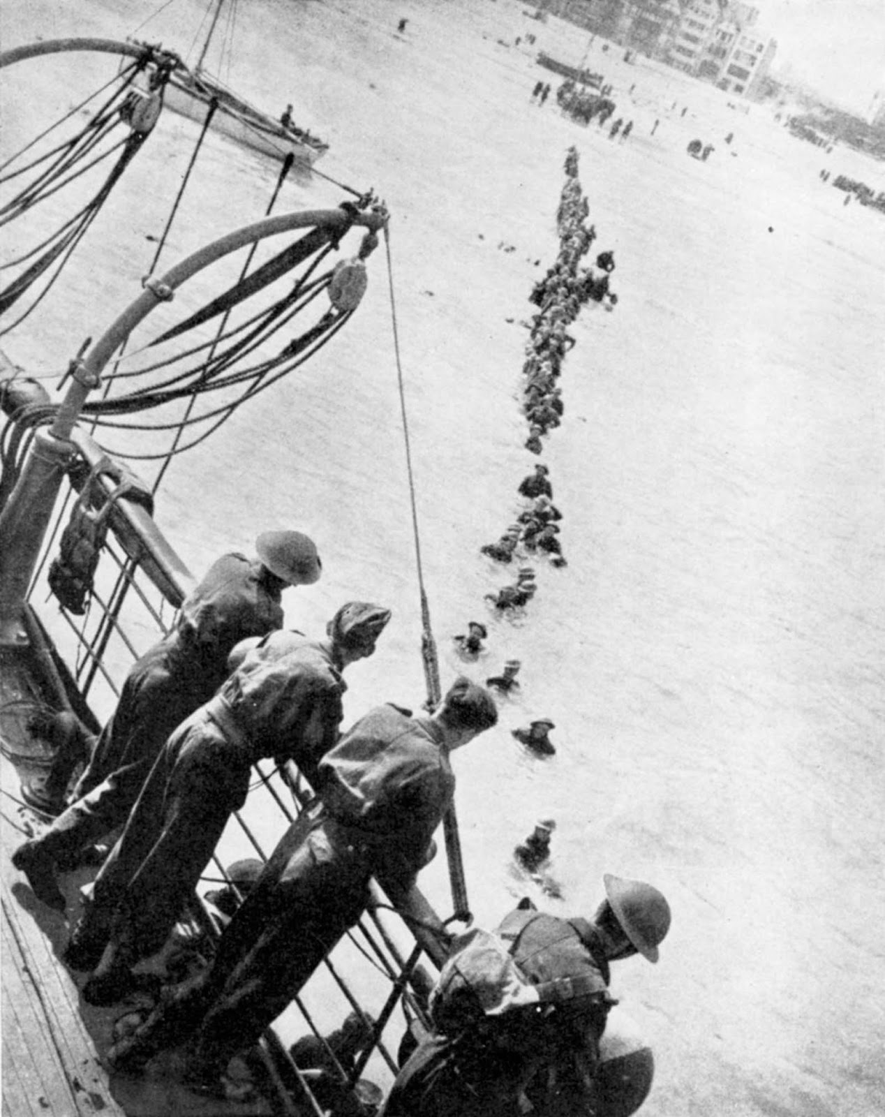 Allied troops wade to evacuation ships off the beach at Dunkirk.