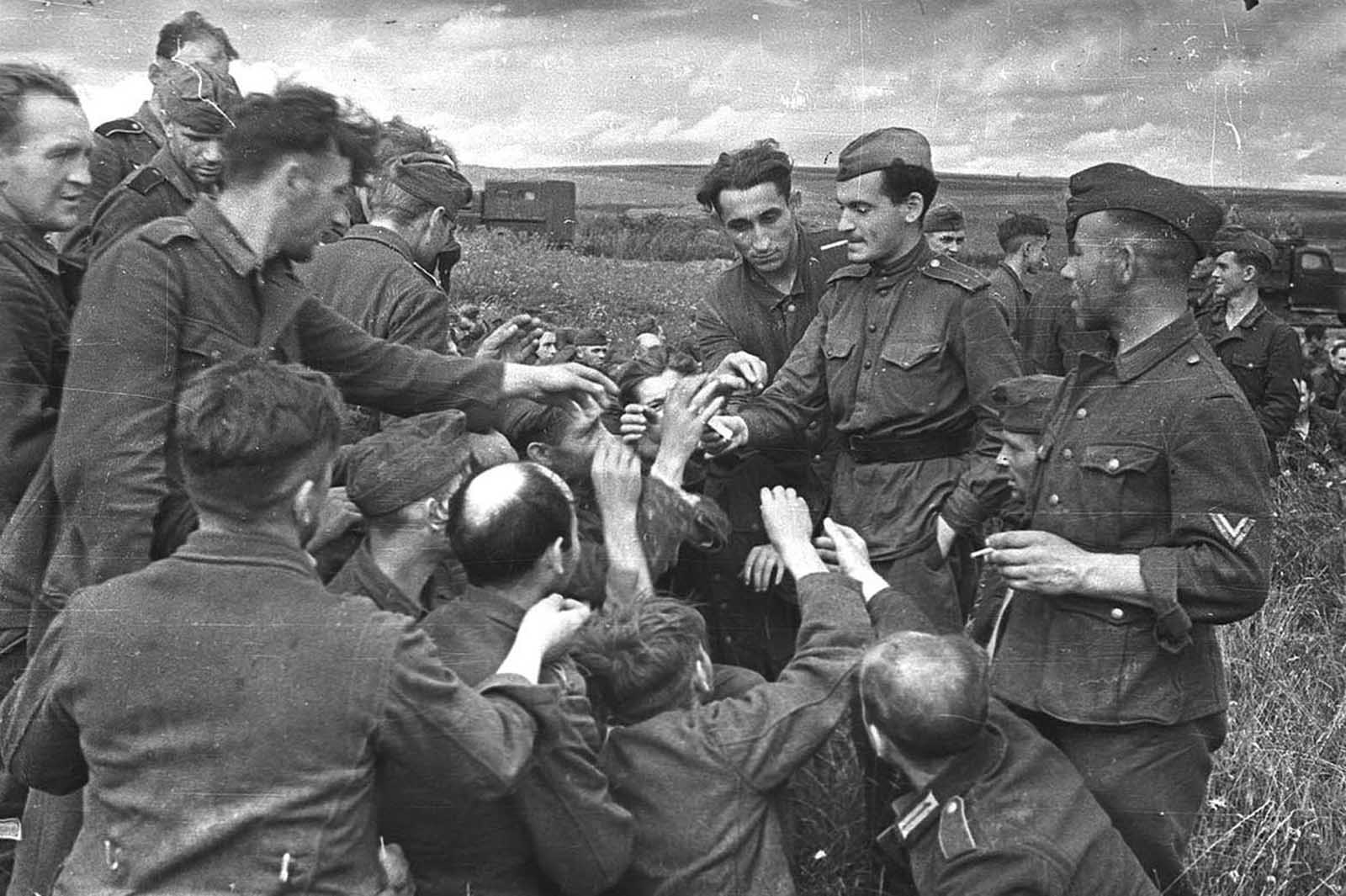 A Soviet lieutenant hands cigarettes to German prisoners somewhere near Kursk, in July of 1943.
