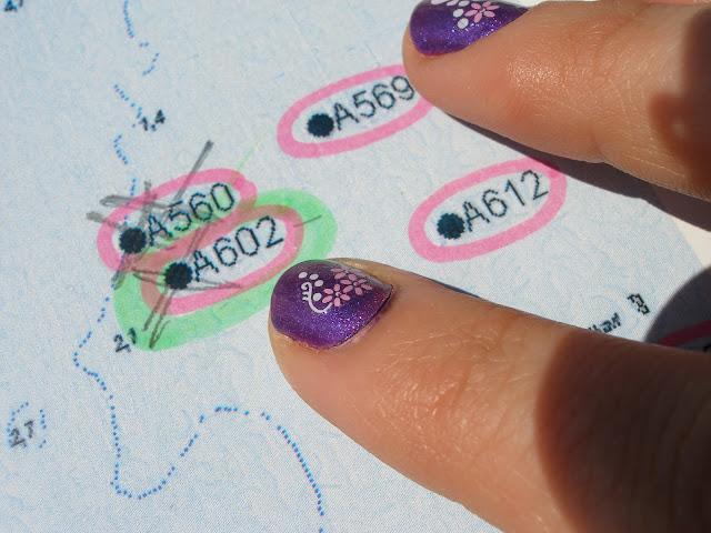 Kartta, jota osoittaa kaksi sormea, joiden kynsilakka on violettia ja kynsissä on kukkakoristeita