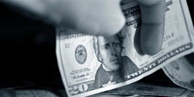 o mână care se pune să ia... o bancnotă de 20 de dolari - imagine preluată de pe christianheadlines.com
