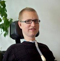 Peter sidder i sin elkørestol med en potteplante i baggrunden. Han har meget kort, lyst hår og firkantede briller og er iklædt en sort sweater. Udenpå er hans respiratorslange synlig.