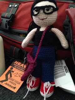 Kwokkie Doll is dressed in travelling clothes: blue jeans, red sneakers, black tank top and glasses. She has a purple satchel slung over her shoulder as she leans on the flight bag of the Little Colourful Teacher