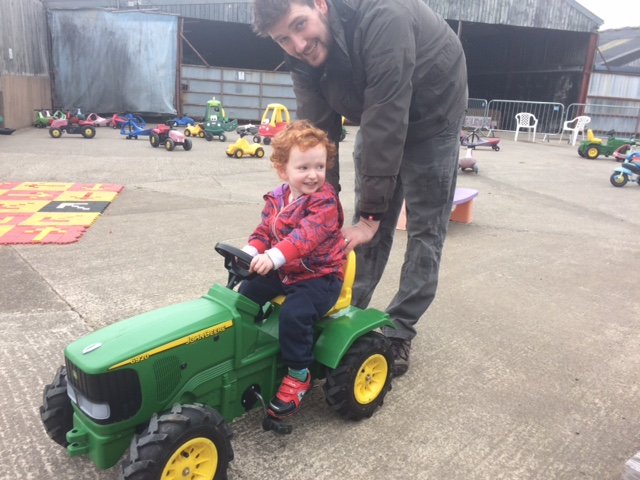 Smiling toddler on a toy tractor being pushed by his Daddy in a yard