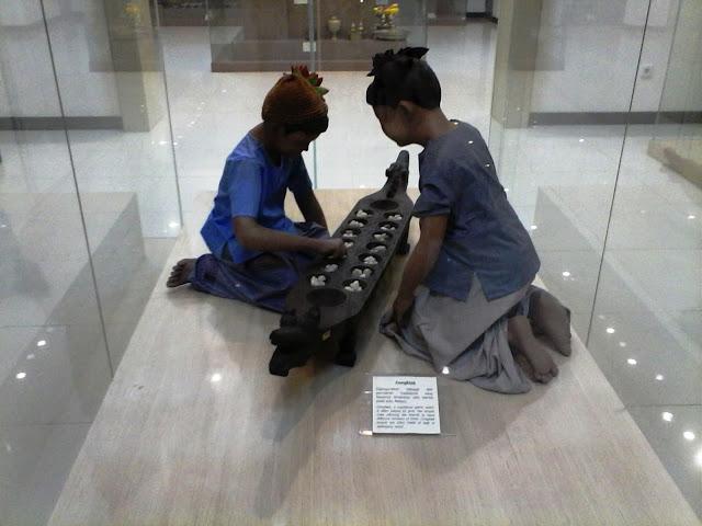 """Satu di antara banyak koleksi Museum Negeri Sumatera Utara berupa replika """"Permainan Tradisional Congkak."""" Congkak adalah sejenis permainan tradisional Melayu menggunakan papan kayu berlubang atau lubang di atas tanah. Buah congkak menggunakan biji getah atau guli"""