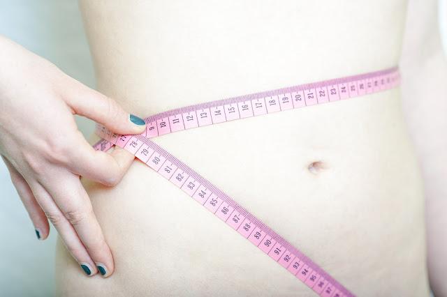 Mujer con cinta métrica en cintura mi hija quiere adelgazar