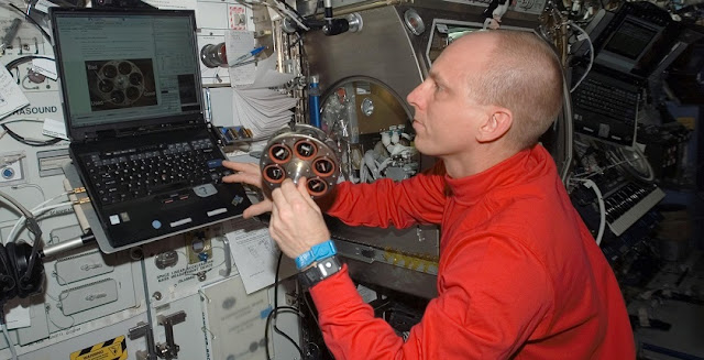 Astronaut Clay Anderson examines a carousel holding material samples in preparation for a smoke detection experiment aboard the International Space Station.  Credit: NASA