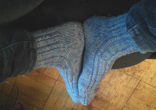 Someone sitting with their feet tucked up on a chair. On their feet is a pair of worsted-weight knitted socks done in a Sky Blue colour. The socks have textured ribbing.