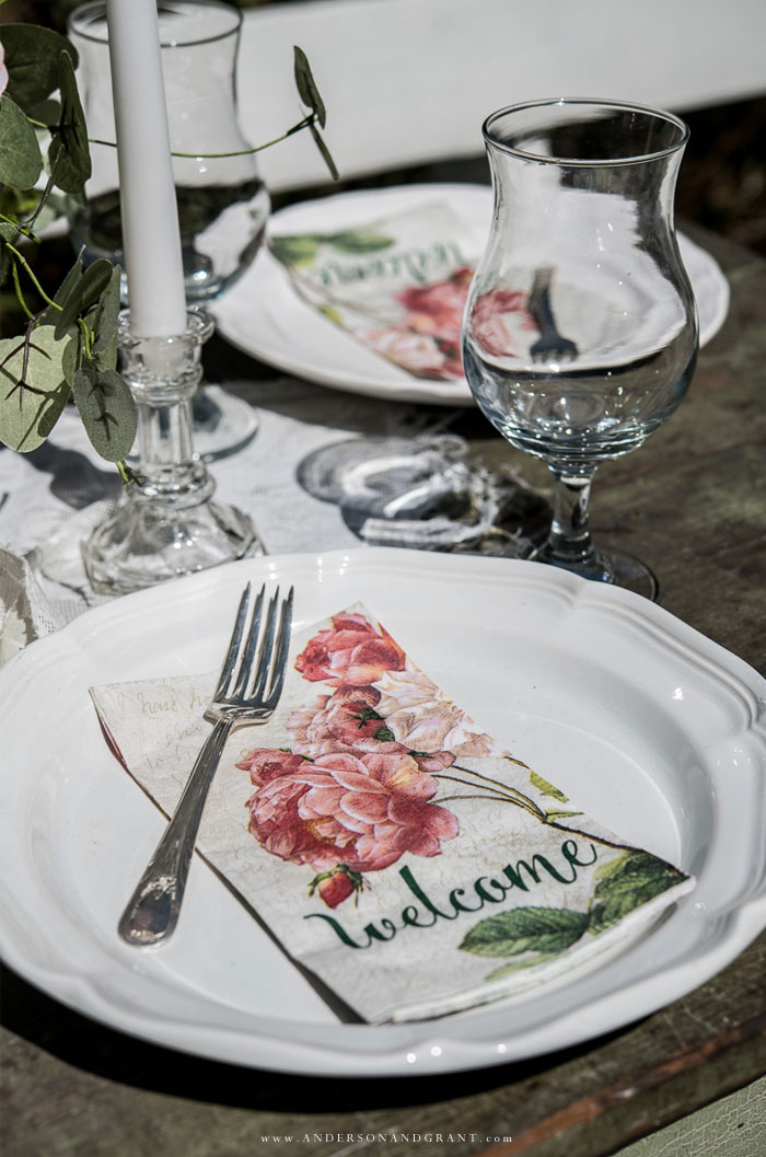 White dining plate with peony napkin and fork