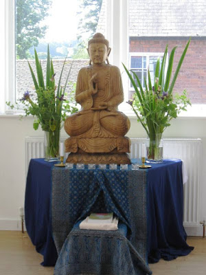 Shrine with Buddha, flowers and candles