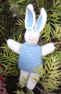 This toy rabbit is the same design as Richard Rabbit. The body and inner ears adn eyes are sky blue; the arms, legs, face and ears are white with a pink embroidered nose. It is sitting amongst the foliage of a grevillea bush.