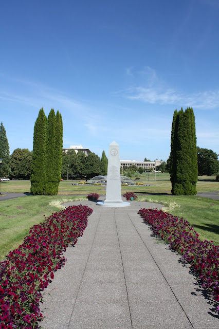 Two rows of flowers lead to the Medal of Honor Monument in Olympia, Washington