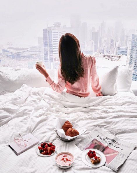 blogger eating breakfast in bed with city views