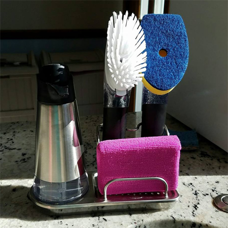 image of a sink organizer on my kitchen countertop, holding a liquid detergent dispenser, a pink sponge, a brush, and a scrubber