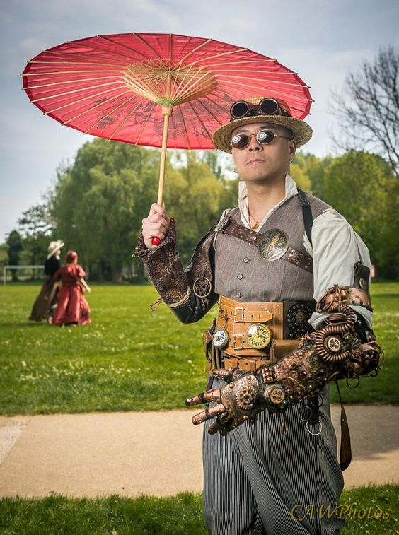 Man wearing Steampunk Victorian clothing which holding a parasol and wearing sunglasses