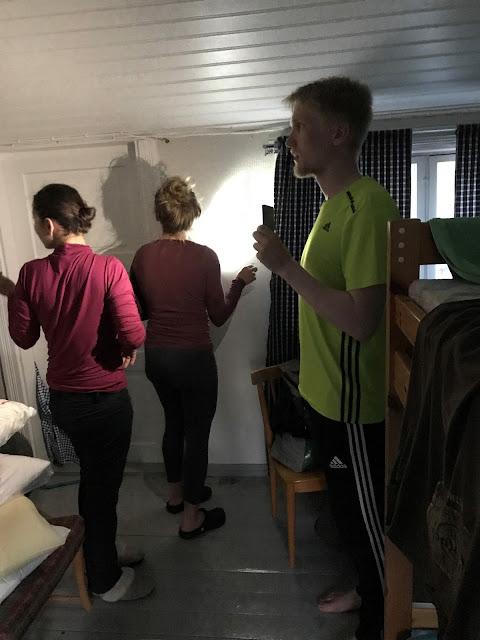 Kolme henkeä tutkii taskulampuilla ja kännyköiden valoilla seiniä