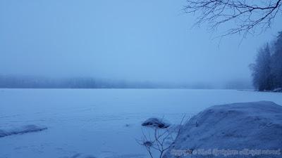Kuva lumen peittämästä jäätyneestä järvestä, jonka yllä leijuu usva