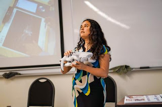 Photo shows Lindsay giving a presentation holding a 3D printed smilodon fossil head at the Annual Pacific Division Meeting in June. Photo by Joan Horvath.