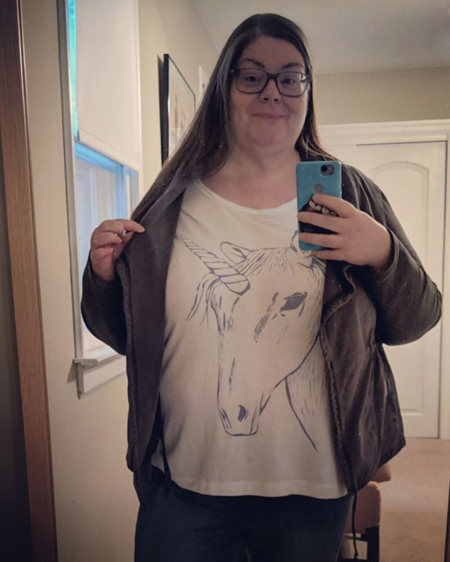 image of me from the waist up standing in a mirror, wearing a grey jacket and a white t-shirt with a unicorn on it; I'm pulling back the lapel of the jacket to reveal the unicorn's horn