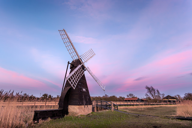 National Trust Wicken Fen wind pump under pastel clouds at sunset