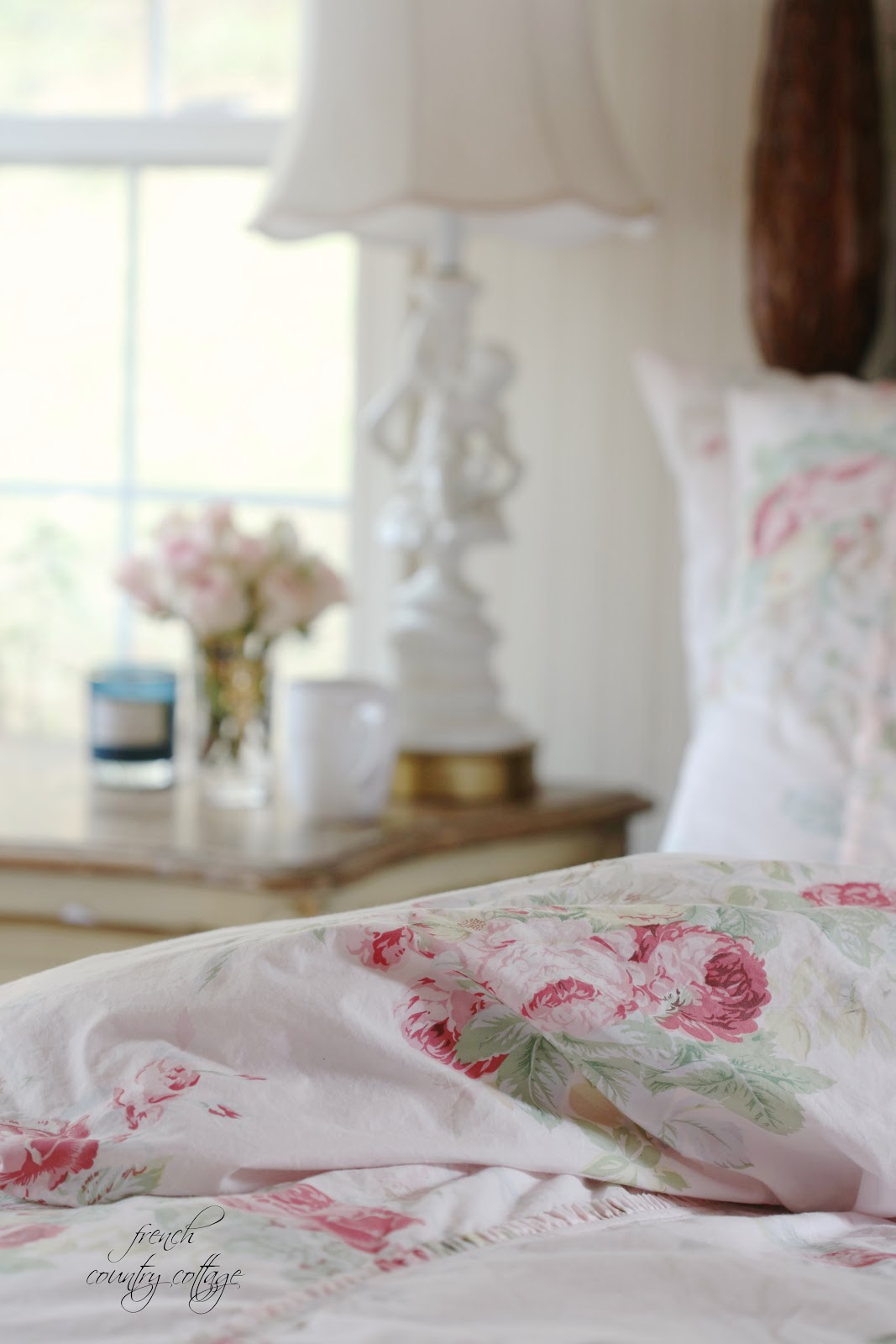 Blush floral bedding with flowers on the nightstand